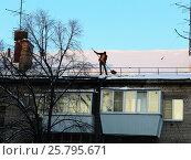 Купить «Рабочий сбрасывает снег с крыши дома», фото № 25795671, снято 29 января 2017 г. (c) Светлана Кириллова / Фотобанк Лори