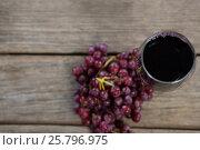 Купить «Overhead of red bunch of grapes with glass of red wine», фото № 25796975, снято 19 декабря 2016 г. (c) Wavebreak Media / Фотобанк Лори