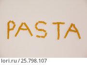 Conchiglie pasta arrange in shape of pasta text. Стоковое фото, агентство Wavebreak Media / Фотобанк Лори