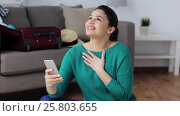 Купить «woman with smartphone and travel stuff at home», видеоролик № 25803655, снято 19 января 2017 г. (c) Syda Productions / Фотобанк Лори