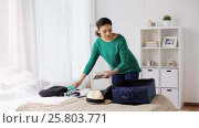 Купить «woman packing travel bag at home or hotel room», видеоролик № 25803771, снято 19 января 2017 г. (c) Syda Productions / Фотобанк Лори