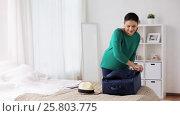 Купить «woman packing travel bag at home or hotel room», видеоролик № 25803775, снято 19 января 2017 г. (c) Syda Productions / Фотобанк Лори