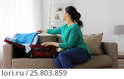 Купить «woman packing clothes to travel bag at home», видеоролик № 25803859, снято 19 января 2017 г. (c) Syda Productions / Фотобанк Лори