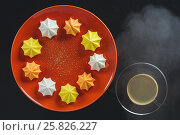 Купить «Multi-colored figured cookies on a round orange plate and a cup of hot coffee on a black background», фото № 25826227, снято 25 марта 2017 г. (c) Anatoly Timofeev / Фотобанк Лори