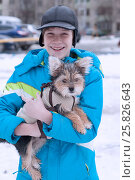 The teenage boy in a jacket walks with a little dog on the street in the winter, фото № 25826643, снято 26 марта 2017 г. (c) Землянникова Вероника / Фотобанк Лори