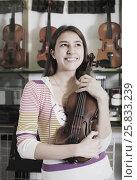 Купить «Girl choosing violin in music shop», фото № 25833239, снято 16 октября 2018 г. (c) Яков Филимонов / Фотобанк Лори