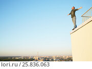 Купить «Young man in denim clothes stands on the edge of the building roof outstretching arms to sides against blue sky», фото № 25836063, снято 12 июня 2015 г. (c) Losevsky Pavel / Фотобанк Лори