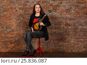 Купить «Pretty young woman with mini guitar sits on stool in studio with red brick wall», фото № 25836087, снято 9 февраля 2016 г. (c) Losevsky Pavel / Фотобанк Лори