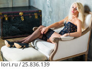 Young blonde woman in a sexy black lingerie and high-heel shoes sits in armchair with her feet on footrest in room. Стоковое фото, фотограф Losevsky Pavel / Фотобанк Лори
