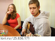 Купить «Young man plays the guitar and sings a song at the table near a girl in the classroom, focus on boy», фото № 25836171, снято 7 марта 2015 г. (c) Losevsky Pavel / Фотобанк Лори