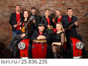 Купить «Brass band of eight people in red and black clothes pose in studio with car couch», фото № 25836235, снято 9 февраля 2016 г. (c) Losevsky Pavel / Фотобанк Лори