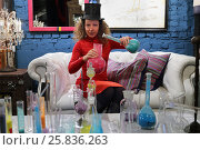 Купить «Woman in hat sitting on couch and holding flasks with colored powder», фото № 25836263, снято 9 марта 2015 г. (c) Losevsky Pavel / Фотобанк Лори