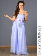 Купить «Beautiful woman in blue long dress smiles and poses in grey studio», фото № 25836283, снято 26 апреля 2015 г. (c) Losevsky Pavel / Фотобанк Лори