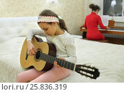 Купить «Two in bedroom: daughter plays guitar and mother playing on synthesizer in background», фото № 25836319, снято 9 марта 2015 г. (c) Losevsky Pavel / Фотобанк Лори
