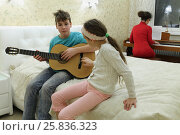 Купить «Three people in bedroom: son playing guitar, daughter sits near him, mother playing on synthesizer in background», фото № 25836323, снято 9 марта 2015 г. (c) Losevsky Pavel / Фотобанк Лори