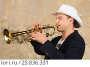 Купить «Young handsome man in white hat and jacket plays trumpet in studio», фото № 25836331, снято 9 февраля 2016 г. (c) Losevsky Pavel / Фотобанк Лори