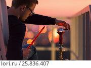 Купить «Young man adjusts cap of hookah sitting in armchair on highrise roof at sunset dusk», фото № 25836407, снято 18 сентября 2015 г. (c) Losevsky Pavel / Фотобанк Лори