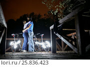Купить «Man and  woman stand embracing at night on wooden platform near bicycles decorated with luminous diodes», фото № 25836423, снято 18 сентября 2015 г. (c) Losevsky Pavel / Фотобанк Лори