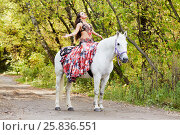 Купить «Young woman dressed in colourful dress decorated with playing cards sits on horseback with arms stretched to sides and face to sky in park», фото № 25836551, снято 20 сентября 2015 г. (c) Losevsky Pavel / Фотобанк Лори