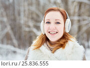 Купить «Humeral portrait of red-haired girl with braces on teeth in earmuffs at winter park», фото № 25836555, снято 25 января 2015 г. (c) Losevsky Pavel / Фотобанк Лори