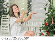 Купить «Portrait of young woman sitting on squatting in courtyard of fake home and throws snow up, smiling. Christmas interior studio», фото № 25836591, снято 14 декабря 2014 г. (c) Losevsky Pavel / Фотобанк Лори
