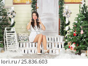 Купить «Full portrait of young woman sitting on threshold of fake home and listening music in headphone, look at us with wonder. Christmas interior studio», фото № 25836603, снято 14 декабря 2014 г. (c) Losevsky Pavel / Фотобанк Лори