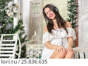 Купить «Portrait of young woman sitting on threshold of fake home and listening music in headphone, smiling and look at us. Christmas interior studio, close-up», фото № 25836635, снято 14 декабря 2014 г. (c) Losevsky Pavel / Фотобанк Лори