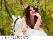 Купить «Young smiling red-haired woman with floral wreath on head lies on horseback in park», фото № 25836675, снято 20 сентября 2015 г. (c) Losevsky Pavel / Фотобанк Лори