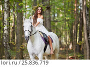Купить «Barefooted girl in white dress with floral wreath on head sits on horseback in park», фото № 25836719, снято 20 сентября 2015 г. (c) Losevsky Pavel / Фотобанк Лори
