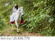 Купить «Young woman in black and white dress rides on horseback in park», фото № 25836779, снято 20 сентября 2015 г. (c) Losevsky Pavel / Фотобанк Лори