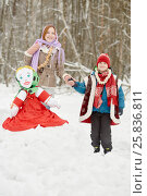 Купить «Teenage girl with shawl on head and boy stand holding hands near stuffed dummy Maslenitsa, sitting on snowbank in winter park», фото № 25836811, снято 25 января 2015 г. (c) Losevsky Pavel / Фотобанк Лори
