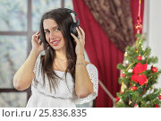 Купить «Half-length portrait of young woman standing near christmas three and listening music in headphone, smiling and look at us. Christmas interior studio, close-up», фото № 25836835, снято 14 декабря 2014 г. (c) Losevsky Pavel / Фотобанк Лори