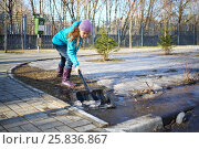 Купить «Girl works with shovel among melted snow, ice at sunny spring day», фото № 25836867, снято 15 марта 2015 г. (c) Losevsky Pavel / Фотобанк Лори