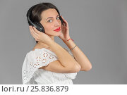Купить «Half-length portrait of woman in white dress in headphones, listen music, looking at us, on gray background», фото № 25836879, снято 14 декабря 2014 г. (c) Losevsky Pavel / Фотобанк Лори