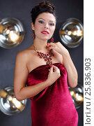 Купить «Beautiful woman poses in red dress near wall with lamps in grey studio», фото № 25836903, снято 15 марта 2015 г. (c) Losevsky Pavel / Фотобанк Лори