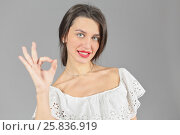 Купить «Half-length portrait of woman in white dress looking at us, making ok hand sign, on gray background», фото № 25836919, снято 14 декабря 2014 г. (c) Losevsky Pavel / Фотобанк Лори