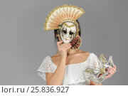 Купить «Half-lengthl portrait of young woman in carnival mask, holding another mask in hand», фото № 25836927, снято 14 декабря 2014 г. (c) Losevsky Pavel / Фотобанк Лори