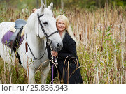 Купить «Blonde woman holds by bridle white horse among the reeds», фото № 25836943, снято 20 сентября 2015 г. (c) Losevsky Pavel / Фотобанк Лори