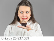 Купить «Half-length portrait of woman holding piece of tasty chocolate cake and wants to eat this cake, on gray background», фото № 25837039, снято 14 декабря 2014 г. (c) Losevsky Pavel / Фотобанк Лори