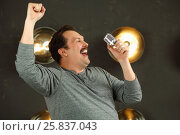 Купить «Smiling man with mustache sings with microphone in studio with lamps on wall», фото № 25837043, снято 15 марта 2015 г. (c) Losevsky Pavel / Фотобанк Лори