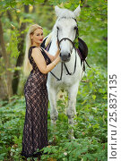 Купить «Woman in long black dress stands near beautiful white horse in park», фото № 25837135, снято 24 сентября 2015 г. (c) Losevsky Pavel / Фотобанк Лори