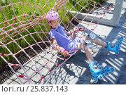 Купить «Girl in pink helmet and rollers sits in net hammock in skate park at summer», фото № 25837143, снято 18 июня 2015 г. (c) Losevsky Pavel / Фотобанк Лори