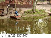 Купить «The boy with a fishing pole sitting on the pier near the pond», фото № 25837567, снято 3 мая 2015 г. (c) Losevsky Pavel / Фотобанк Лори