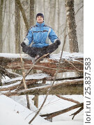 Man sits on fallen trunk in forest meditating during snowfall on winter day, фото № 25837583, снято 19 марта 2016 г. (c) Losevsky Pavel / Фотобанк Лори