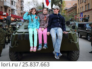 Купить «SAMARA - MAY, 6, 2015: Boy and two girls (with model releases) sitting on armored vehicle in Samara during military celebration. Red Square is not affected by military equipment on parade May 9th», фото № 25837663, снято 6 мая 2015 г. (c) Losevsky Pavel / Фотобанк Лори