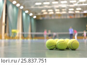 Купить «Some tennis balls on tennis court in sports hall, blurred background», фото № 25837751, снято 9 февраля 2015 г. (c) Losevsky Pavel / Фотобанк Лори