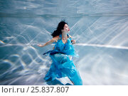 Купить «Young black-haired woman in blue dress poses underwater», фото № 25837807, снято 14 мая 2016 г. (c) Losevsky Pavel / Фотобанк Лори