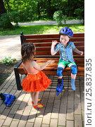 Купить «Little girl plays with boy sitting on bench in helmet in summer park», фото № 25837835, снято 24 июня 2015 г. (c) Losevsky Pavel / Фотобанк Лори