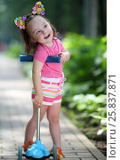 Купить «Little pretty girl in shorts poses with scooter in summer sunny park», фото № 25837871, снято 24 июня 2015 г. (c) Losevsky Pavel / Фотобанк Лори