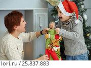 Купить «Happy boy takes out sock gift and mothre looks at he near christmas tree, focus on woman», фото № 25837883, снято 24 декабря 2014 г. (c) Losevsky Pavel / Фотобанк Лори